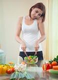 Jonge Aziatische vrouw in keuken en het spreken op de mobiele telefoon Stock Fotografie