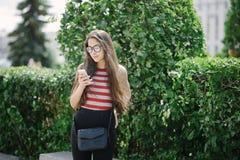 Jonge Aziatische vrouw met glazen gebruikend smartphone en verzendend sms Stock Foto