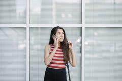 Jonge Aziatische vrouw met het spreken op smartphone dichtbij glasmuur Stock Afbeeldingen