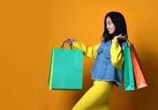 Jonge Aziatische vrouw met het winkelen zakken op kleurenachtergrond royalty-vrije stock foto's