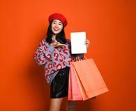 Jonge Aziatische vrouw met het winkelen zakken op kleurenachtergrond royalty-vrije stock afbeeldingen
