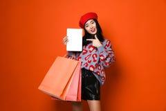Jonge Aziatische vrouw met het winkelen zakken op kleurenachtergrond stock afbeeldingen