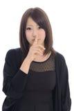 Jonge Aziatische vrouw met stiltegebaar Stock Afbeeldingen