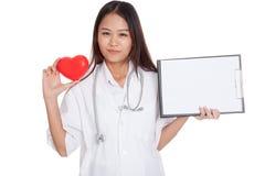 Jonge Aziatische vrouwelijke arts met rood hart en leeg klembord Royalty-vrije Stock Afbeelding