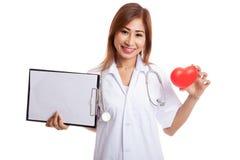 Jonge Aziatische vrouwelijke arts met rood hart en leeg klembord Stock Afbeeldingen
