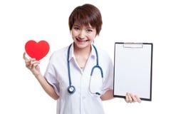 Jonge Aziatische vrouwelijke arts met rood hart en leeg klembord Royalty-vrije Stock Foto