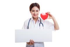 Jonge Aziatische vrouwelijke arts met rood hart en leeg klembord Stock Fotografie