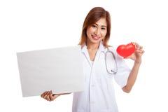 Jonge Aziatische vrouwelijke arts met rood hart en leeg teken Royalty-vrije Stock Foto's