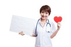 Jonge Aziatische vrouwelijke arts met rood hart en leeg teken Stock Afbeeldingen