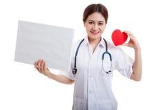 Jonge Aziatische vrouwelijke arts met rood hart en leeg teken Stock Foto's