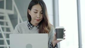 Jonge Aziatische vrouwelijke manager gebruikend draagbaar computerapparaat en drinkend koffiekop terwijl het zitten op het modern stock videobeelden