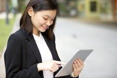 Jonge Aziatische vrouwelijke uitvoerende gebruikende tabletpc Royalty-vrije Stock Afbeeldingen