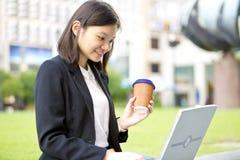 Jonge Aziatische vrouwelijke uitvoerende het drinken koffie en het gebruiken van laptop PC Royalty-vrije Stock Afbeelding