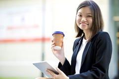 Jonge Aziatische vrouwelijke uitvoerende het drinken koffie en het gebruiken van tabletpc Stock Afbeeldingen