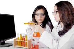 Jonge Aziatische vrouwelijke wetenschappers die chemische producten mengen Stock Foto
