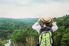 jonge Aziatische vrouwenreiziger met rugzak het ontspannen op mountian en het kijken bos royalty-vrije stock foto