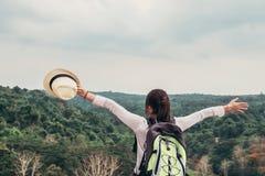 jonge Aziatische vrouwenreiziger met rugzak het ontspannen op mountian en het kijken bos stock foto