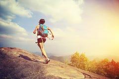 Jonge Aziatische vrouwenwandelaar die op bergpiek lopen Royalty-vrije Stock Afbeelding