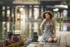 Jonge Aziatische vrouwenzitting op een rivierdok Stock Foto's