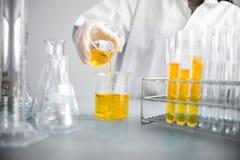 Jonge Aziatische wetenschapper die met reageerbuis onderzoek naar klinisch laboratorium maken De wetenschap, de chemie, de techno stock afbeeldingen