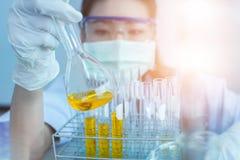 Jonge Aziatische wetenschapper die met reageerbuis onderzoek naar klinisch laboratorium maken De wetenschap, de chemie, de techno stock fotografie