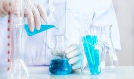 Jonge Aziatische wetenschapper die met reageerbuis onderzoek naar klinisch laboratorium maken De wetenschap, de chemie, de techno Stock Foto