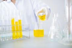 Jonge Aziatische wetenschapper die met reageerbuis onderzoek naar klinisch laboratorium maken De wetenschap, de chemie, de techno Stock Foto's