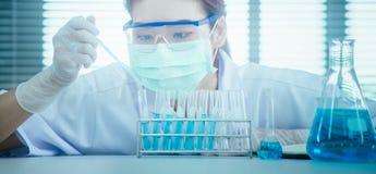 Jonge Aziatische wetenschapper die met reageerbuis onderzoek naar klinisch laboratorium maken De wetenschap, de chemie, de techno stock afbeelding
