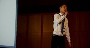 Jonge Aziatische zakenman die in bedrijfsseminarie bij auditorium 4k spreken stock video