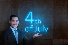 Jonge Aziatische zakenman die het gloeien licht van 4 van Juli tonen stock afbeeldingen
