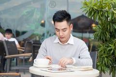 Jonge Aziatische zakenman die met documenten bij koffie werken Royalty-vrije Stock Afbeelding
