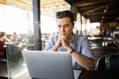 Jonge Aziatische zakenman die met laptop computer en notitieboekje in koffie toevallige ondernemer werken Het freelance werk stock afbeelding