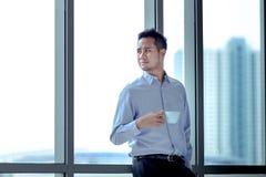 Jonge Aziatische zakenman die zich tegen die venster bevinden in zijn h wordt ontspannen royalty-vrije stock afbeeldingen