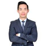 Jonge Aziatische zakenman die zijn wapens kruisen stock fotografie