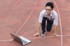 Jonge Aziatische zakenman met laptop klaar beginpositie om op rasspoor door:sturen De concurrentie en visie bedrijfsconcept stock afbeelding
