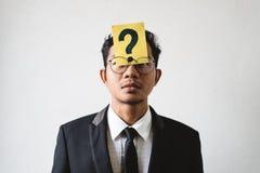 Jonge Aziatische zakenman met VRAAGTEKEN op zijn voorhoofd stock afbeelding