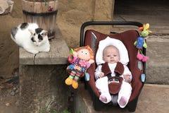 Jonge baby, zuigeling in een miniatuurautozetel stock afbeelding
