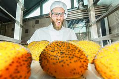 Jonge bakker die bij verse hete broodjes met papaverzaden schreeuwen op de bakkerijachtergrond stock afbeeldingen