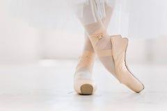 Jonge ballerina, close-up op benen en schoenen, die zich in pointepositie bevinden stock afbeelding