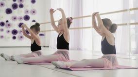 Jonge ballerina's die hun flexibiliteit opleiden stock video