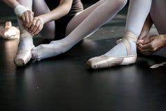 Jonge ballerina's die hun pointes aanzetten stock foto