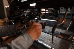 Jonge barista maakt smakelijke hete koffie in een professionele koffiemachine De moderne koffiemachine giet espresso in een zwart royalty-vrije stock afbeeldingen