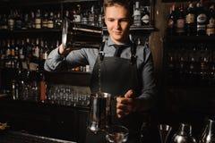Jonge barman die een duidelijke alcoholische drank op de barteller gieten royalty-vrije stock foto