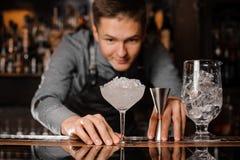 Jonge barman die het cocktailglas bekijken die met ijs wordt gevuld stock foto's