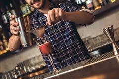Jonge barman die zich bij bar tegen het maken vrolijke cocktail bevinden royalty-vrije stock afbeeldingen