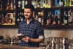Jonge barman die zich bij bar tegen plaatsende orde bevinden op digitale vrolijke tablet stock foto