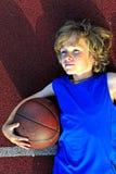 Jonge basketbalspeler die een bal houden Stock Afbeelding