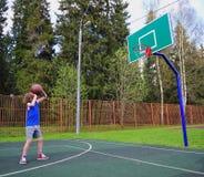 Jonge basketbalspeler die een bal voorbereidingen treffen te werpen Stock Fotografie
