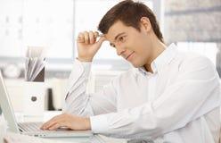 Jonge beambte die in bureau met laptop denkt Royalty-vrije Stock Foto