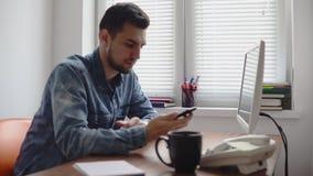 Jonge beambte die zijn telefoon bij de bureauzitting bij de lijst met computer, telefoon en het drinken koffie of thee gebruiken stock footage